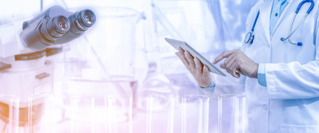 Medical science research and development concept - Doctor holding tablet computer with scientific instrument, microscope and  chemical test tube in lab background.
