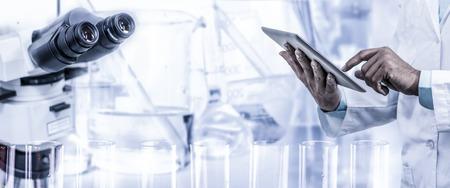 Wetenschapsonderzoek en technologieconcept - de tabletcomputer van de Wetenschapperholding met wetenschappelijk instrument, microscoop en chemische reageerbuis op laboratoriumachtergrond.