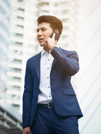 Business man speaking on phone against city business building background. Concept of business phone call and communication technology.