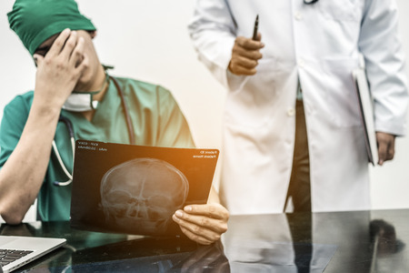 Medical Failure Concept - Surgical doctor covering his face with hand (face palm) expressing disappointment while holding xray film on office desk.
