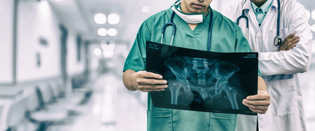 Doctor and surgeon examining xray film, diagnose patient 's waist bone injury. Surgery operation and medical banner design.
