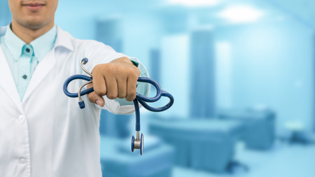 Male doctor holding stethoscope, smiling on hospital background. Healthcare service, general practice and medical career concept.
