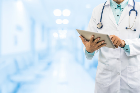 Male doctor working on computer tablet in the hospital or office background. Concept of medical data analysis and healthcare business.