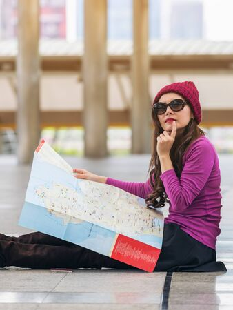 map case: Woman traveller looking at travel map in airport walkway with bag or luggage. She is lost or using map to plan travel route for the next destination. Concept of single woman travel alone.