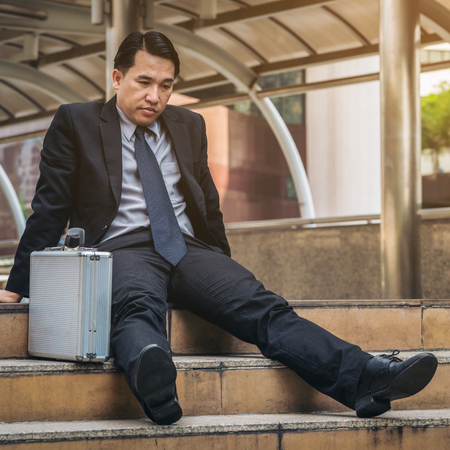 jobless: Desperate businessman sitting hopelessly on stair floor in central business district due to unemployment. Concept of failure, desperation, unemployment and business depression. Stock Photo