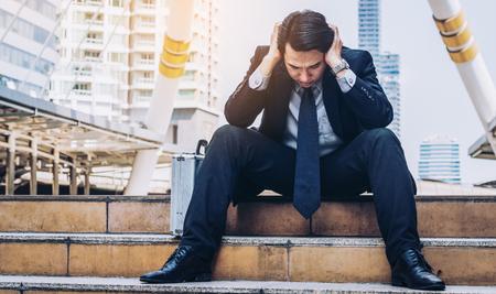 Verzweifelter Geschäftsmann, der hoffnungslos auf Treppenfußboden im zentralen Geschäftsgebiet wegen der Arbeitslosigkeit sitzt. Konzept des Scheiterns, Verzweiflung, Arbeitslosigkeit und Wirtschaftskrise.