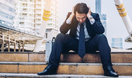 Desperate businessman sitting hopelessly on stair floor in central business district due to unemployment. Concept of failure, desperation, unemployment and business depression. Stockfoto