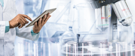 Science research and technology concept - Scientist holding tablet computer with scientific instrument, microscope and chemical test tube in lab background. Stock Photo
