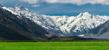 Beautiful landscape of mountain ranges and green grass meadow field under white clouds in the blue sky in sunny summer day. Shot in Mt Cook, the highest mountain in New Zealand. Zdjęcie Seryjne