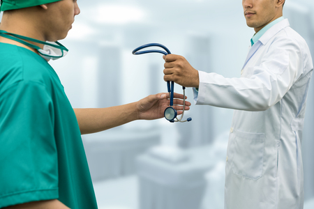 Doctor passing stethoscope to surgeon. Concept of specialist referral patients from general practitioner GP for further medication.