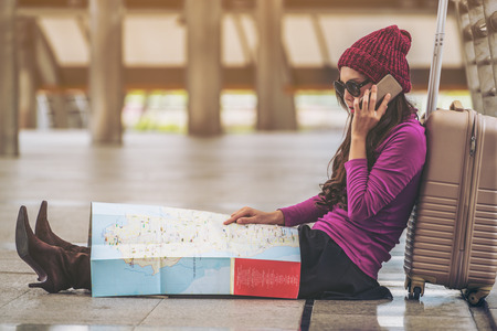 Lost woman traveller making phone call asking for help while looking at the map. Travel problem and lost concept. Travel lifestyle.