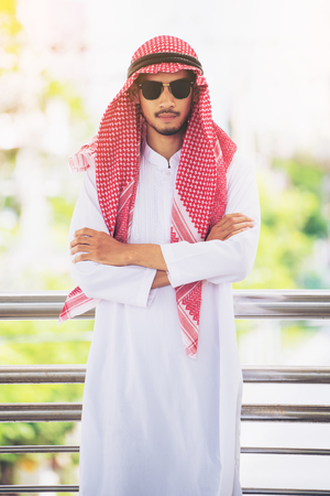 thobe: Arab man or businessman crossed arms looking at camera. Arabic business concept.