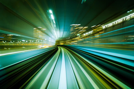 Motion blurred front view of train running in modern city tunnel. Abstract transportation background. Stock Photo