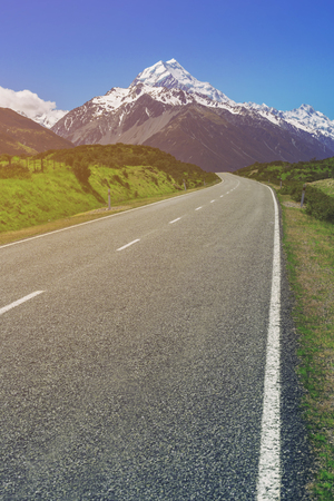 Road to Mt Cook and mountain landscape. Concept of road trip travel in New Zealand. Empty highway or freeway leading to Mount Cook, the highest mountain in New Zealand.
