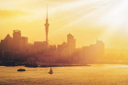 Golden sunset at Auckland city skyline with silhouette of city center and Auckland Sky Tower, the iconic landmark of Auckland, New Zealand. Stock Photo
