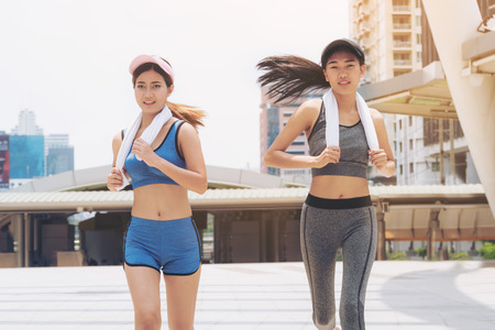Two healthy woman running in the city background. Concept of women fitness, healthy urban lifestyle and urban running.