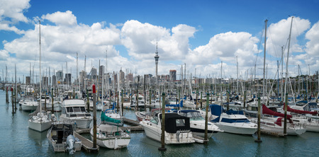 Yacht at harbour in Auckland with city skyline and Auckland Sky Tower, the iconic landmark of Auckland, New Zealand.
