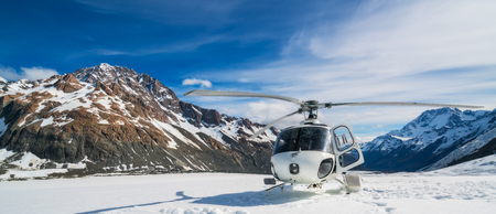 Helicopter landing on snow mountain in tasman glacier in Mt Cook, New Zealand. The helicopter service in Mt Cook offers scenic flights, glacier landing and emergency rescue.