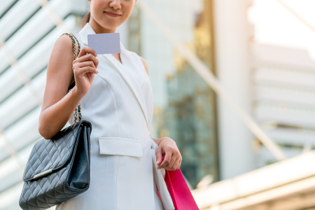 Businesswoman showing white empty card in modern city buildings background. Concept of business card, credit card or insurance card for working woman.