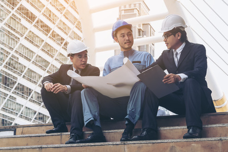 construction project: Engineer, architect, business man discuss on engineering blueprint drawing. Concept of architecture, construction engineering and business people group meeting.