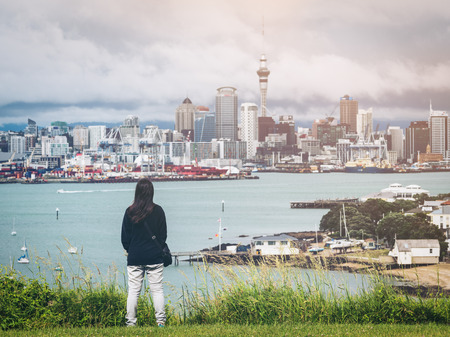 Young woman looking at Auckland city skyline of city center and Auckland Sky Tower in New Zealand. Stock Photo