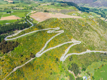 Winding Road on Mountains near Queenstown, New Zealand from aerial view by drone flying over Crown Range Road east of Queenstown in Otago, South Island of New Zealand. Standard-Bild