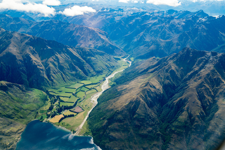 Aerial view of mountain ranges and lake landscape. Panoramic shot from airplane flying above mountains near Lake Wakapitu in Queenstown, New Zealand.