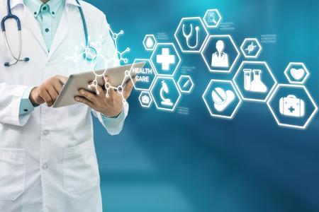 Concepto médico de la atención sanitaria - Doctor en hospital con la interfaz moderna de los iconos médicos que muestra el símbolo de la medicina, de la innovación, del tratamiento médico, del servicio de emergencia, de los datos doctorales y de la salud del paciente. Foto de archivo