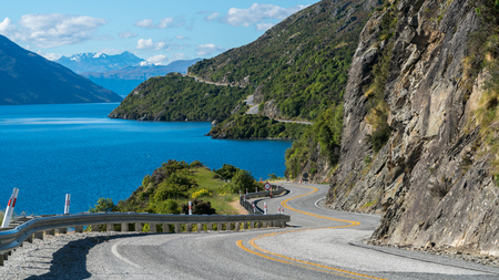 Winding road along mountain cliff and lake landscape in Queenstown, New Zealand South Island. Travel and road trip in summer. Stock Photo