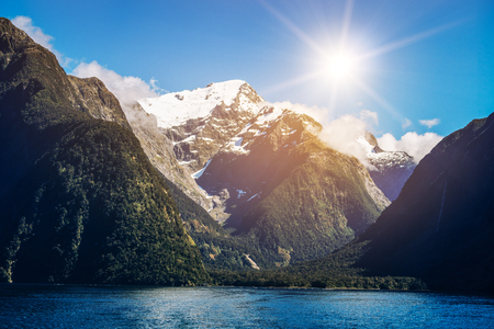 Lake and mountain landscape with snow capped peak under summer sunlight in blue sky background. Shot in Milford Sound, Fiordland National Park, South Island of New Zealand.