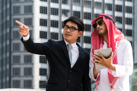 Arab man and business man discussion, pointing at business target. Multicultural oversea business and target setting.