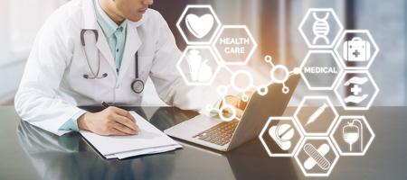 Concepto médico: el médico que trabaja en el hospital con una computadora y escribe documentos ilustrados con íconos médicos aparecen de la mano de los médicos sobre negocios de farmacia de atención médica y educación doctoral.