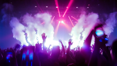 Happy people dance in nightclub party concert and listen to music from DJ on the stage in background. Cheerful crowd celebrate Christmas and New Year party 2018. Young people lifestyle and nightlife. Stock Photo