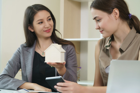 Real estate agent, financial adviser or insurance sales person is talking about house buying, mortgage loan or insurance protection to her client in the office. Stock Photo