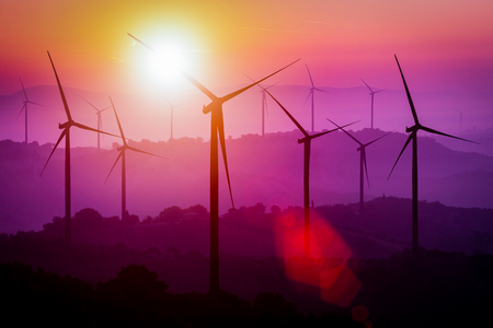 Wind turbines silhouette on mountains at sunset. Concept of renewable clean energy and sustainability development business from wind energy.