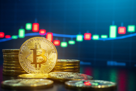Bitcoin and cryptocurrency trading system concept - Image of Physical bitcoin pile against market price chart as blur background.