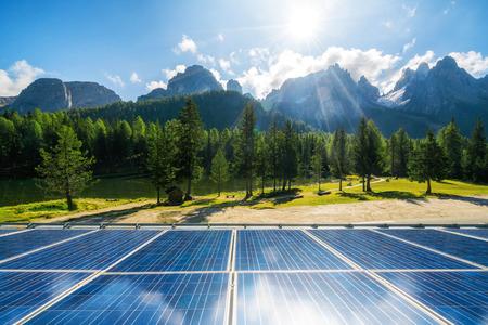 Zonnecelpaneel in landlandschap tegen zonnige hemel en bergachtergronden. Zonne-energie is de innovatie voor de duurzaamheid van wereldenergie. Duurzame bronnen. Stockfoto