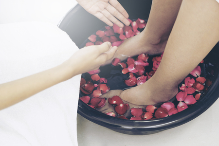 Foot spa massage treatment by professional massage therapist in luxury spa resort. Wellness, stress relief and rejuvenation concept.