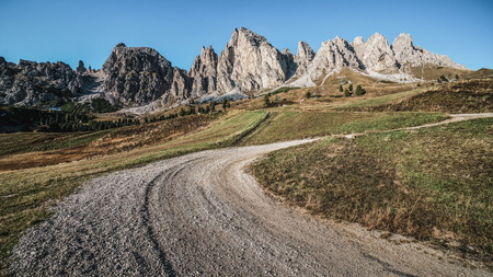 Dirt road and hiking trail track in Dolomites mountain, Italy, in front of Pizes de Cir Ridge mountain ranges in Bolzano, South Tyrol, Northwestern Dolomites, Italy. Stock Photo