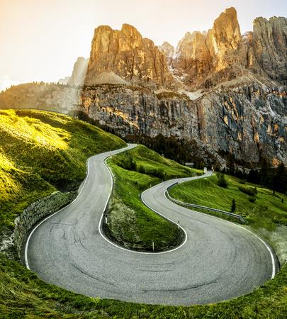 Hermoso camino de montaña con árboles, bosques y montañas en el fondo. Tomado en la carretera estatal en Passo Gardena, grupo de montaña Sella de montaña Dolomitas en Italia. Foto de archivo