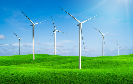 Wind turbines farm on a green grass rolling hills against blue sky and white clouds in summer. Concept of renewable clean energy and sustainability business development.