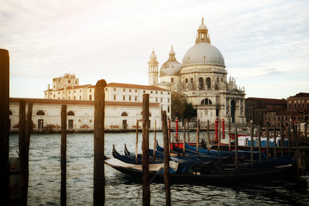 Gondola boats in Venice Italy with gorgeous view of Basilica Santa Maria della Salute. Venice is famous travel destination in Italy for its unique cityscape and culture.