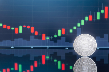 Initial coin offering (ICO) and digital money investing concept - Physical metal digital coins with blue global trading exchange market price chart in the background.