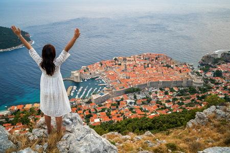 Traveller looking at view of Dubrovnik city, in Dalmatia, Croatia, the prominent travel destination of Croatia.
