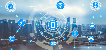 Smart city wireless communication network with graphic showing concept of internet of things ( IOT ) and information communication technology ( ICT ) against modern city buildings in the background.