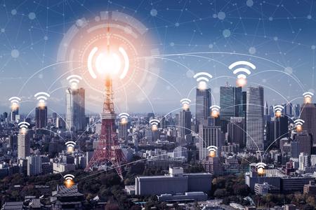 Inteligentna miejska bezprzewodowa sieć komunikacyjna z grafiką przedstawiającą koncepcję internetu rzeczy (IOT) i technologii teleinformatycznej (ICT) na tle nowoczesnej zabudowy miejskiej. Zdjęcie Seryjne