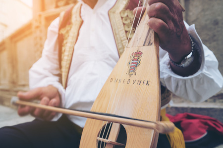 A busker plays traditional Croatian folk music with a 3-string instrument (lijerica) in the old city of Dubrovnik, Croatia.