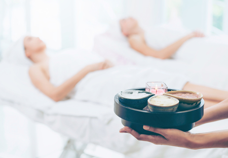 Massage therapist holding spa treatment set and hot scrub lotion with woman lying on spa bed prepared for spa massage in background. Luxury wellness, stress relief and rejuvenation concept.