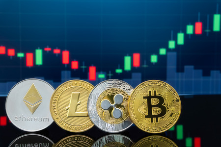 Bitcoin and cryptocurrency investing concept - Physical metal Bitcoin coins with global trading exchange market price chart in the background.