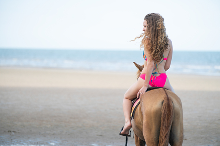 Woman fashion model riding a horse on the beach in summer. Luxury travel vacation.